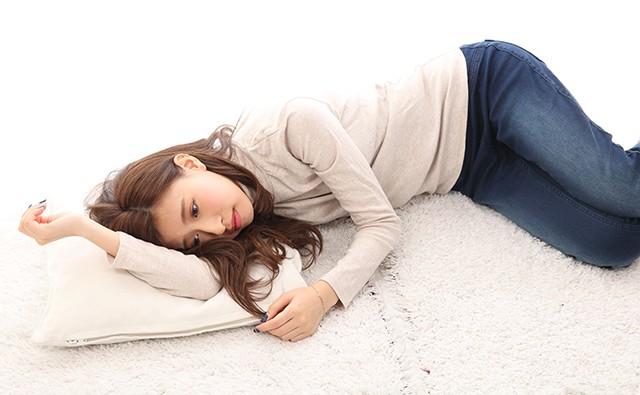 生理痛でつらそうに横たわる女性